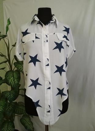 Белая блуза с коротким рукавом и звездным принтом.