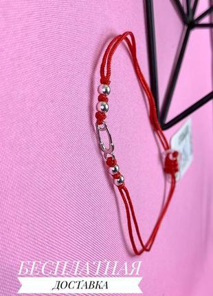Красный браслет с серебряной булавочкой