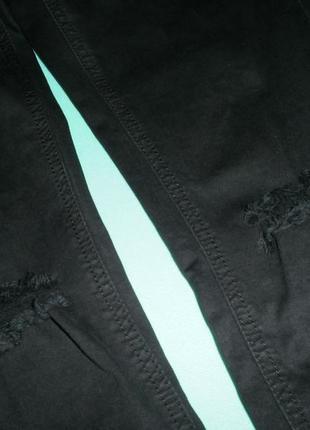 Черные джинсы с дырками на коленях.