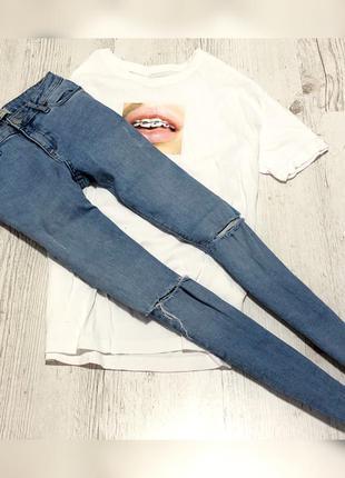 Голубые джинсы с фабричными дырками на коленах