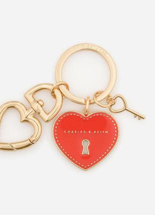 Золотой брелок с ключом и сердцем.