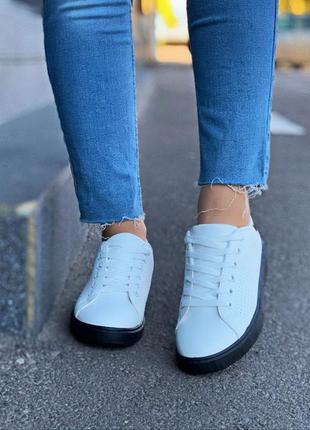 Белые кроссовки на черной подошве