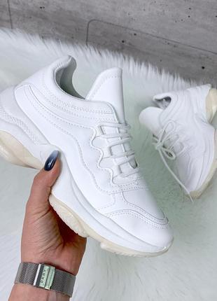 Белые кроссовки на массивной подошве.