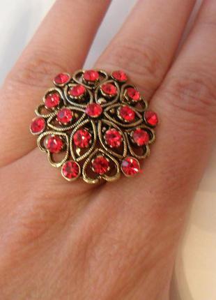 Крупное кольцо с красными стразами.