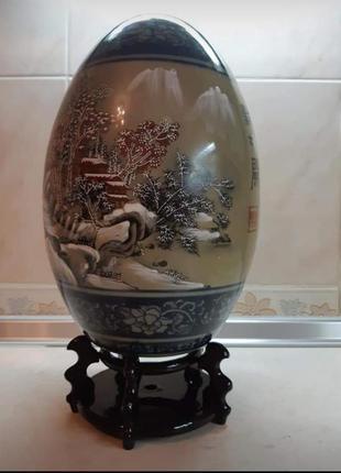 Статуэтка в виде декоративного расписного яйца на деревянной п...