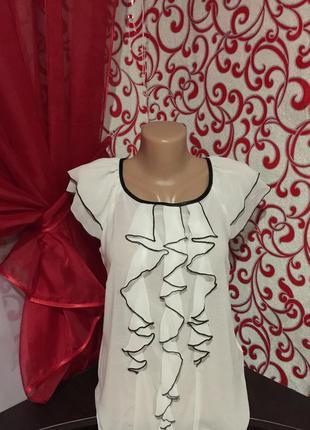 Белая воздушная блузка  без рукавов с двойным воланом на рукав...