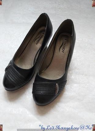 Симпатичные туфли на танкетке в чёрном цвете, сбоку с украшени...