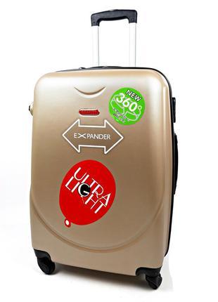 Бронзовый большой пластиковый четырехколесный чемодан на колес...