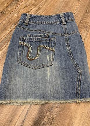 Джинсовая  актуальная юбка с потертостями  и  необработанным к...