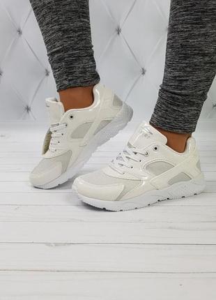 Белые кроссовки с лаковыми вставками.