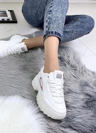 Белые кроссовки на высокой подошве.