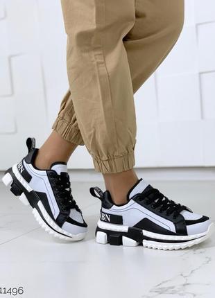 Стильные белые кроссовки с чёрными вставками.