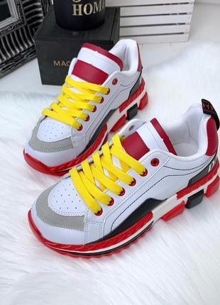 Стильные белые кроссовки с красными вставками.