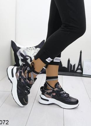 Стильные чёрные кроссовки с белой подошвой.