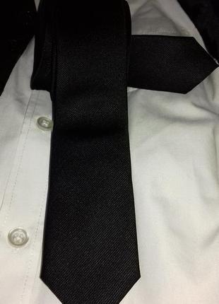 Узкий черный галстук, в рубчик.