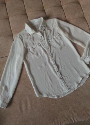 Белая школьная блузка с металлическими заклёпками на воротнике...
