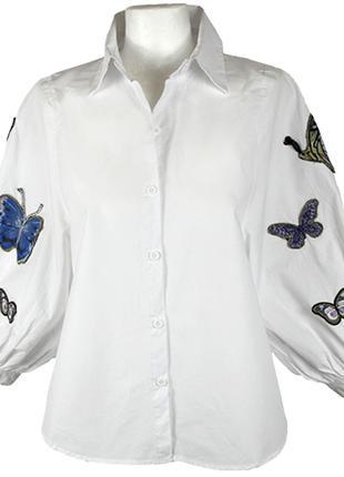 Белая рубашка с пышными рукавами и нашивками на рукавах.