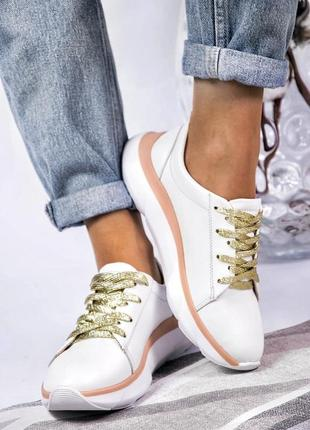 Белые кожаные кроссовки с золотистыми шнурками.