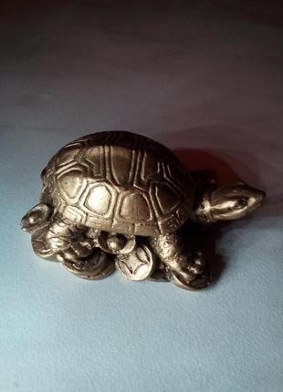 Статуэтка - золотая черепаха на монетах.