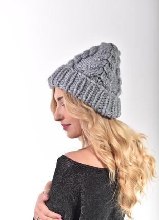 Женская шапка крупной вязки с косами
