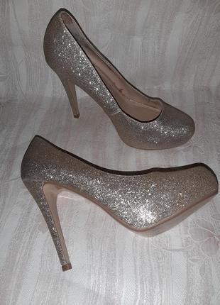 Золотистые блестящие туфли на высоком каблуке