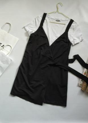 Комплект из черного ромпера платья и белой v-образной футболки...