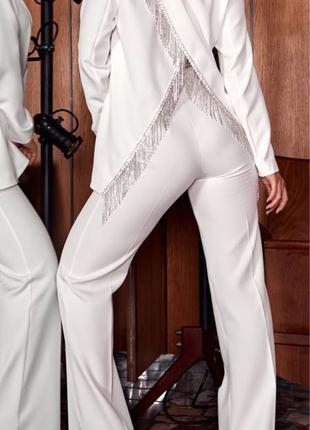 Брючный белый костюм с разрезом на пиджаке
