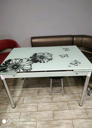 Стеклянный стол на хромированных ножках.