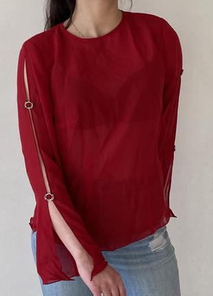 Красная блузка з кольцами на рукавах
