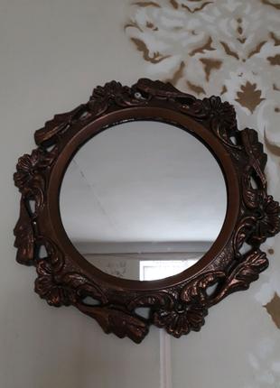Дзеркало в литій металлічній оправі.