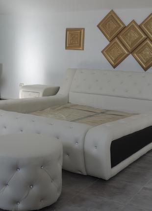 Красивая мягкая кровать -подиум возле окна