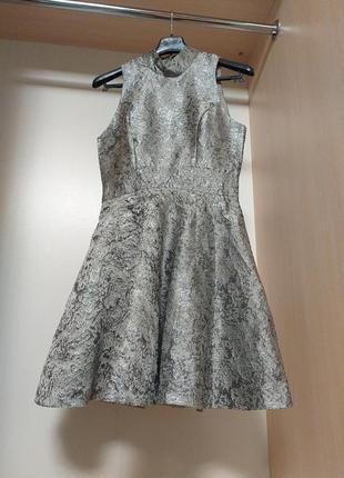 Платье из серебряной парчи с пышной юбкой и вырезом на спине