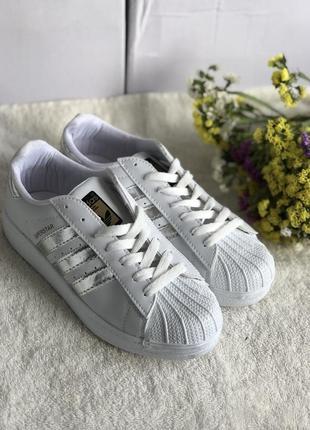 Белые кроссовки с серебряными полосками