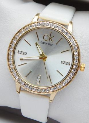 Женские наручные часы на белом кожаном ремешке с камушками вок...