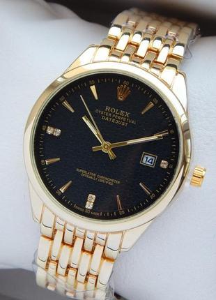 Солидные наручные часы золотого цвета с черным циферблатом, от...