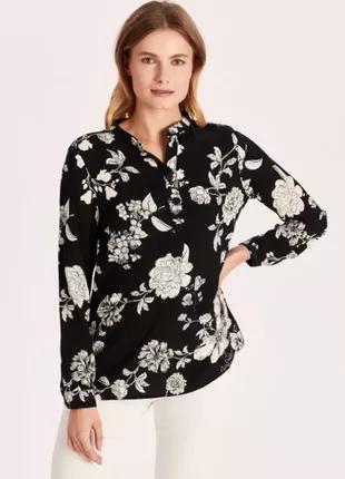 Женская блуза черного цвета с цветочным принтом.