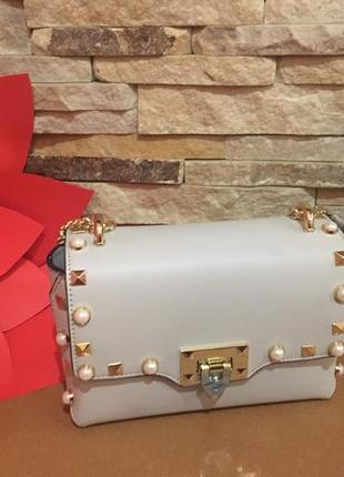 Красивая кожаная сумочка молочного цвета украшена жемчужинками.