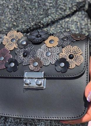 Небольшая кожаная сумочка, украшена цветочками.