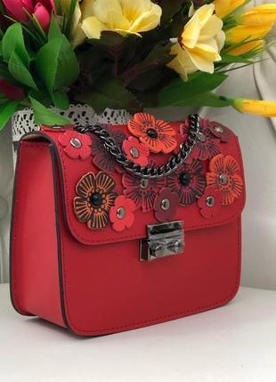 Кожаная сумочка украшена цветочками.
