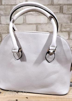 Белая сумка держит форму